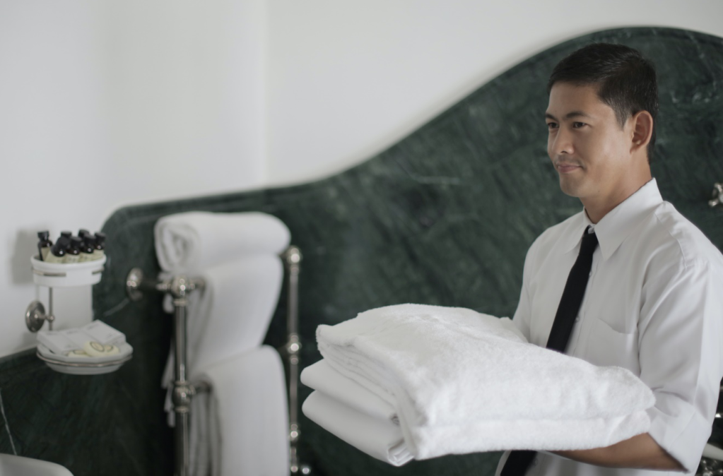 A hotel staff member carrying clean towels