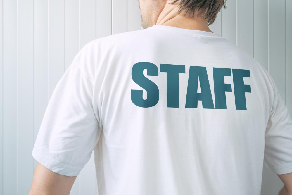 White shirt with staff written on the back.